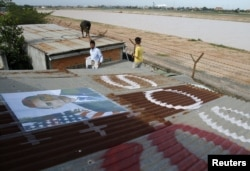 People display portraits of U.S. President Barack Obama on the roof of their houses near Phnom Penh Airport November 14, 2012.