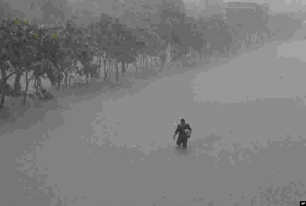 A man crosses a flooded highway in the financial district of Makati, south of Manila, Philippines, August 20, 2013.
