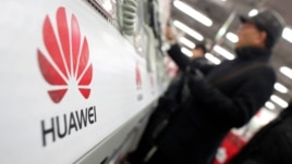 A man looks at a Huawei mobile phone as he shops at an electronic market in Shanghai, Jan. 22, 2013.