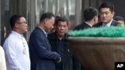 Philippine President Rodrigo Duterte, center walks out from a shopping mall in Beijing, China, Wednesday, Oct. 19, 2016.