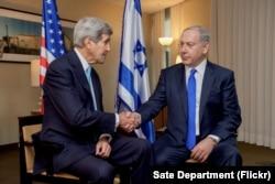 ລັດຖະມົນຕີຕ່າງປະເທດສະຫະລັດ ທ່ານ John Kerry ຈັບມືກັບ ນາຍົກລັດຖະມົນຕີ ອິສຣາແອລ ທ່ານ Benjamin Netanyahu ຫຼັງຈາກທີ່ພວກເພິ່ນ ໄດ້ກ່າວຖະແຫລງ ຕໍ່ສື່ມວນຊົນ ກ່ອນຈະຈັດກອງປະຊຸມສອງຝ່າຍ ໃນນະຄອນ Berlin, ປະເທດເຢຍຣະມັນ, ວັນທີ 22 ຕຸລາ 2015.