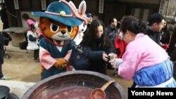 동지 절기를 이틀 앞둔 지난 20일 경기 용인시 한국민속촌에서 관람객들에게 팥죽을 나눠주고 있다.
