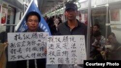 赵海通(右)2013年年初在广州地铁上举牌 (民生观察图片)