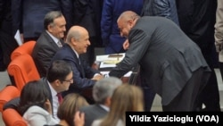 Son oylamanın ardından Tuğrul Türkeş'in, kabinedeki görevi için ayrıldığı parti sıralarına gitmesi ve eski lideri MHP Genel Başkanı Devlet Bahçeli ile samimi görüntüsü dikkat çekti.
