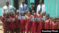 FILE: Children with some teachers at Musengezi Primary School displaying some of the books sourced from overseas donors.