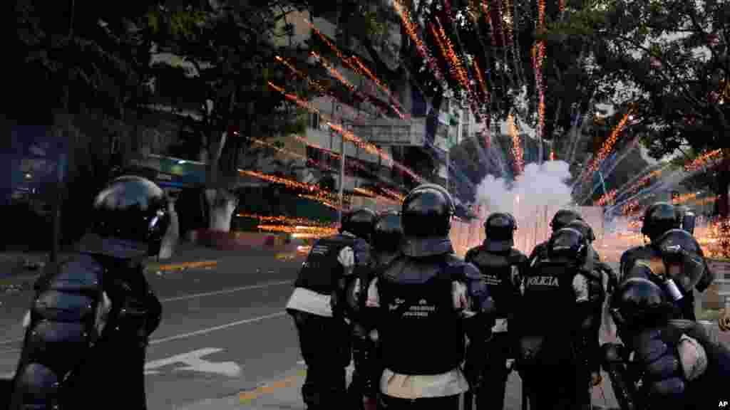 Policías se protegen de la explosión de una bomba molotov lanzada por los manifestantes, en los disturbios de Caracas.