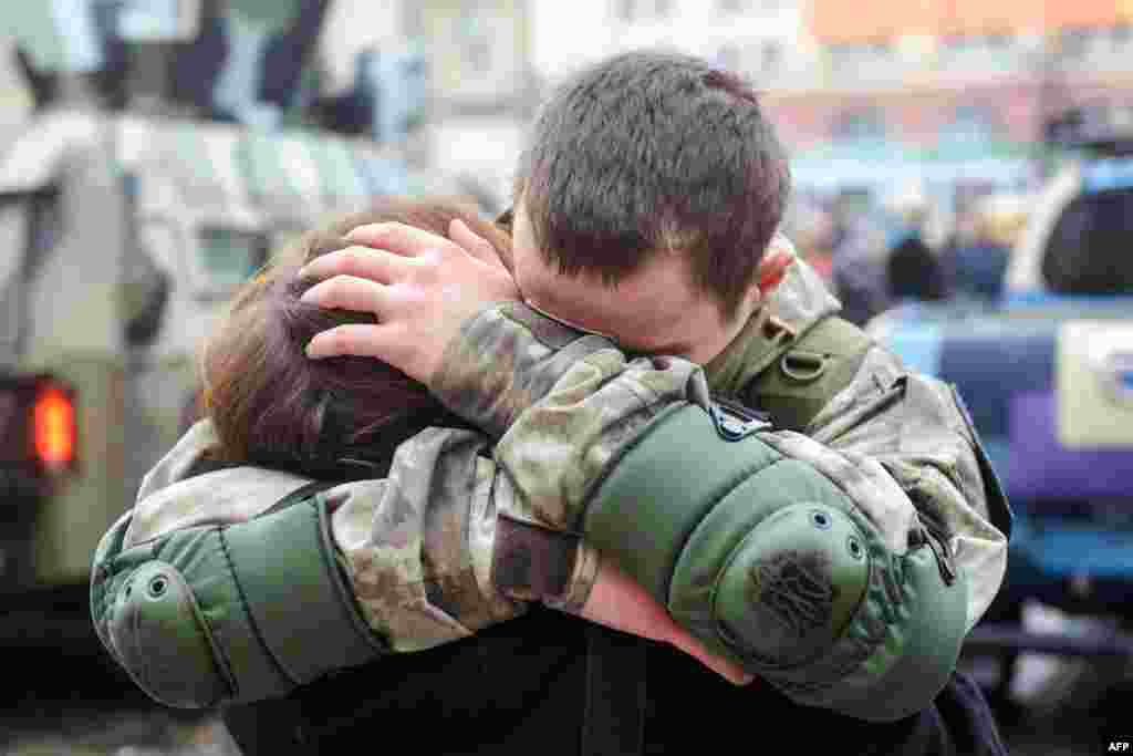 "A Ukrainian policeman embraces his wife during a ceremony in Kharkiv, northeastern Ukraine, before his departure to the east of the country where he will take part in an ""Anti-Terrorist Operation"" (ATO)."