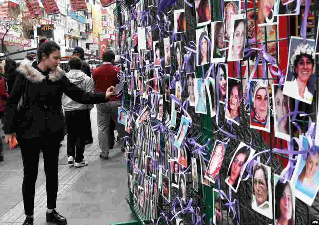 A woman looks at a photo exhibition of murdered women staged as a protest in Ankara, Turkey, ahead of International Women's Day on March 8, 2015.