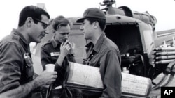In this undated photo taken some time in the early to mid 1960s, from L to R, reporters David Halberstam (New York Times), Malcolm Brown (Associated Press) and Neil Sheehan (UPI) chat beside a helicopter in Vietnam.