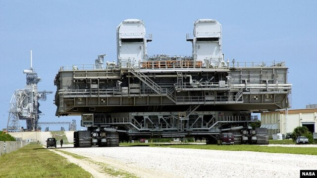 A mobile launch platform is taken to the launch pad by a NASA crawler-transporter.