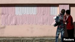 4月7日两名阿富汗男孩看投票站墙上贴的初选名单
