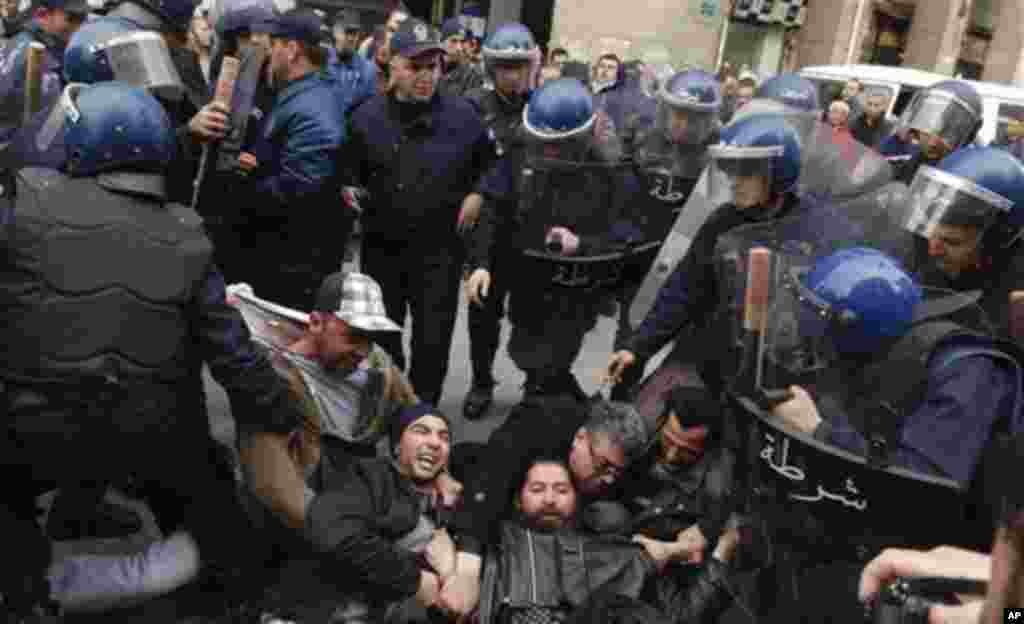 Protesters are removed by riot police officers during a protest in Algiers, Algeria, February 19, 2011. (AP Image)