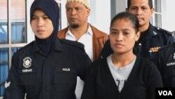 Wilfrida Soik (kanan) dikawal oleh polisi Malaysia saat memasuki ruang sidang Mahkamah Tinggi di Kota Bharu, negara bagian Kelantan hari Senin 30/9 (foto: VOA/Munarsih).