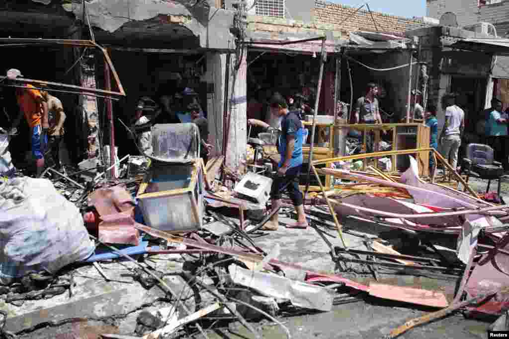 Residents inspect the site of a car bomb attack in Basra, Iraq, July 29, 2013.