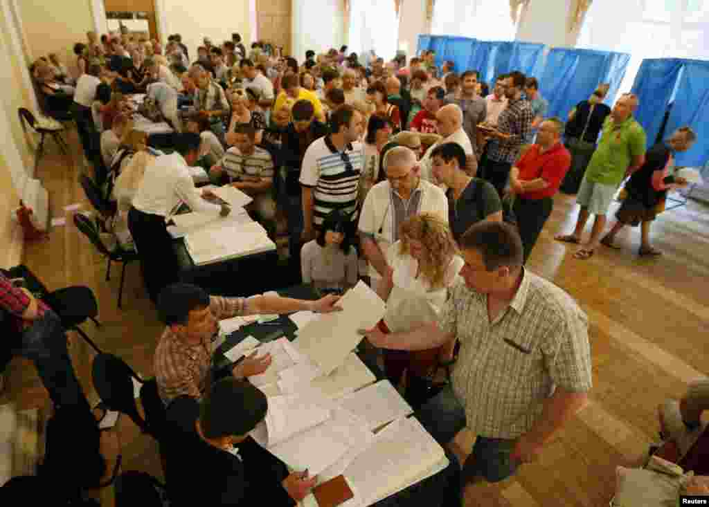 People queue to collect their ballot papers during voting in a presidential election at a polling station in Kyiv, May 25, 2014. Ukrainians voted in a presidential election billed as the most important since they won their independence from Moscow 23 years ago.