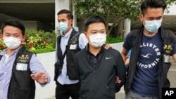 2021年6月17日,香港《蘋果日報》總編輯羅偉光(右二)遭警方逮捕,該報另有四名高管也於同日被捕。(AP圖片)