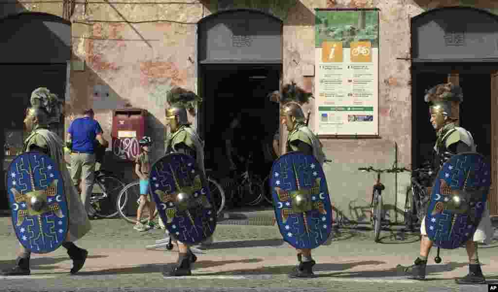 مردانی در لباس روم باستان، در مقابل بنای آپیان وی در روم رژه می روند.