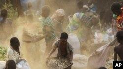 Femmes et enfants séparant la terre du grain renversé par un camion dont le conducteur a perdu le contrôle, dans la forêt de Machinga au Malawi, 24 mai 2016. (AP Photo/Tsvangirayi Mukwazhi)