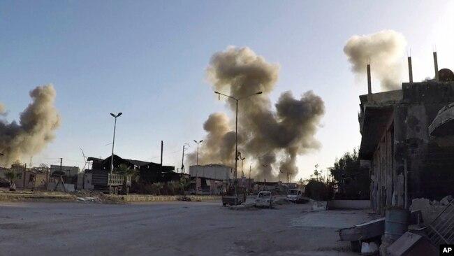Esta foto de los Cascos Blancos de Defensa Civil siria, muestra que el humo sube tras los ataques aéreos del gobierno sirio en la ciudad de Douma, en la región este de Ghouta.