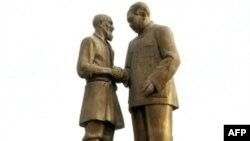 Синьцзян: местный житель стоит у памятника Мао Цзэдуну и уйгурскому крестьянину Курбану Тулуму, некогда встретившегося с создателем КНР