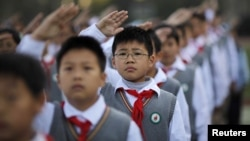 Young Pioneers salute during the weekly flag-raising ceremony at the East Experimental School in Shanghai November 5, 2012. Created in 1949, the Young Pioneers movement is considered a seedbed for future members of the Chinese Communist Party, and consist