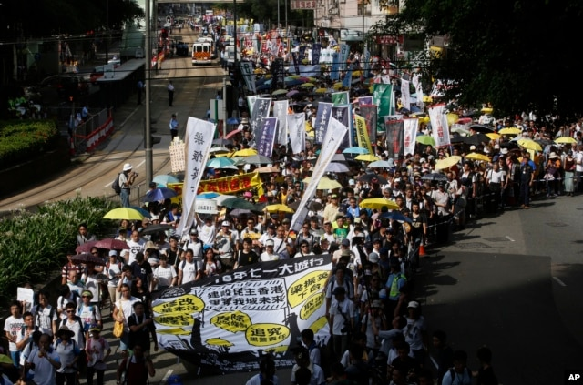 FILE - Pro-democracy protesters march during an annual protest marking Hong Kong's handover from British to Chinese rule in 1997 in Hong Kong, Wednesday, July 1, 2015. In 2014, millions of pro-democracy protesters blocked Hong Kong's streets for several weeks.