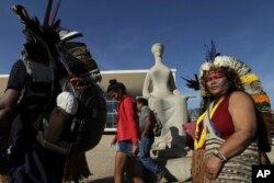 Indians walk past a statue of justice as they protest outside the Supreme Court, in Brasilia, Brazil, Aug. 16, 2017. Brazil's indigenous communities protested as the Supreme Court deliberated on the legality of President Michel Temer's plan to restrict land titles awarded to the communities.