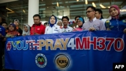 Members of a youth group holds roses and a banner as they pray for the missing Malaysia Airlines Boeing 777-200 plane at a hotel in Putrajaya on March 10, 2014.