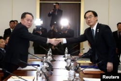Head of the North Korean delegation, Ri Son Gwon shakes hands with South Korean counterpart Cho Myoung-gyon as they exchange documents after their meeting at the truce village of Panmunjom in the demilitarized zone separating the two Koreas, South Korea, Jan. 9, 2018.
