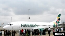 FILE - Journalists gather next to a Nigerian Eagle Airlines plane during its launch in Nigeria's commercial capital of Lagos, Sept. 18, 2009.