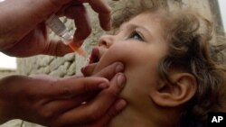 Afg'onistonlik bola poliomielitga qarshi vaksina olmoqda, Kobul, Afg'oniston, 2006-yil, 5-mart