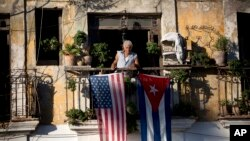 FILE - Javier Yanez stands on his balcony in Old Havana, where he hung U.S. and Cuban flags after learning that the two nations would begin restoring diplomatic ties.