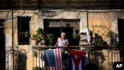 在哈瓦那旧城,一位市民在得知美古两国将恢复邦交后,高兴地挂出两国国旗。