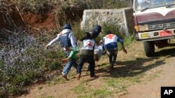 In this Feb. 17, 2015, photo provided by the Eleven Media Group, Myanmar red-cross members carry an injured victim during a clash between government troops and Kokang rebels in Kokang, northeastern Shan State, more than 800 kilometers (500 miles) northeast of Yangon, Myanmar.