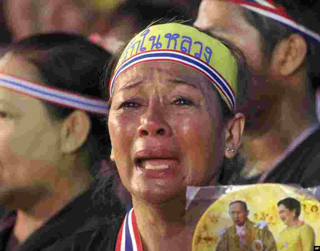 Holding a picture of Thai King Bhumibol Adiulyadej and Queen Sirikit, an anti-government protester cries during a demonstration in Bangkok, Nov. 11, 2013.