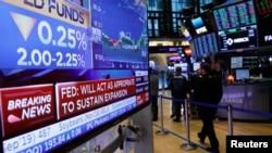 Sebuah layar menampilkan pengumuman suku bunga Federal Reserve AS ketika para pedagang bekerja di lantai New York Stock Exchange (NYSE) di New York, AS, 31 Juli 2019. (Foto: Reuters/Brendan McDermid)