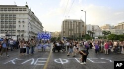 A protester writes graffiti which reads 'Thieves'' outside the Greek Parliament during a peaceful rally for a 15th day, called through a social networking site in Athens, June 8, 2011