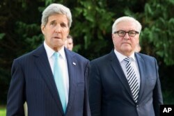 U.S. Secretary of State John Kerry, left, walks with German Foreign Minister Frank-Walter Steinmeier, prior to a meeting with a group of refugees fleeing Syria, at Villa Borsig, in Berlin, Sept. 20, 2015.