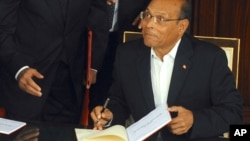 Tunisian President, Moncef Marzouki reacts as he signs the new Constitution in Tunis, Jan. 27, 2014