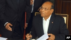 FILE - Tunisian President Moncef Marzouki reacts as he signs the new Constitution in Tunis, Jan. 27, 2014