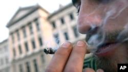 Un hombre fuma marihuana frente al Parlamento de Uruguay mientras los diputados debatían la legallización del cannabis.
