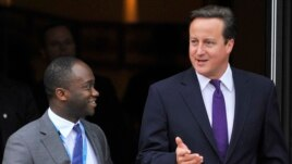 On Oct. 5, 2011, Britain's Prime Minister David Cameron, right, walks with Conservative MP Sam Gyimah on the final day of the Conservative Party's annual conference in Manchester, England.