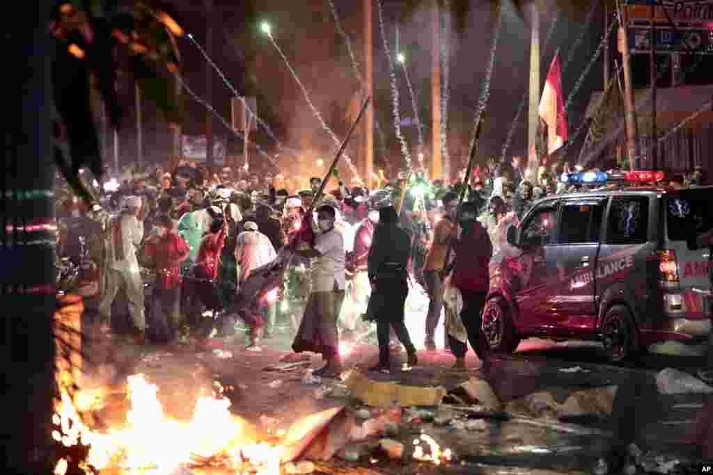 Fire crackers explode near supporters of presidential candidate Prabowo Subianto during clashes with the police in Jakarta, Indonesia. President Joko Widodo said authorities have the situation under control after six people died in the riots.