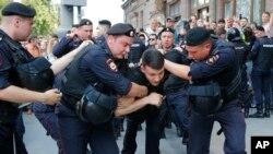 Policías detienen a un hombre durante un mitin no autorizado en el centro de Moscú, el sábado 27 de julio de 2019. Los manifestantes exigían que se permitiera a los candidatos de la oposición postularse para el concejo municipal de Moscú.