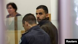 Hikmat Massarwa (R), a member of Israel's Arab minority, attends a remand hearing at the Central District Court in Lod, near Tel Aviv Apr. 25, 2013.