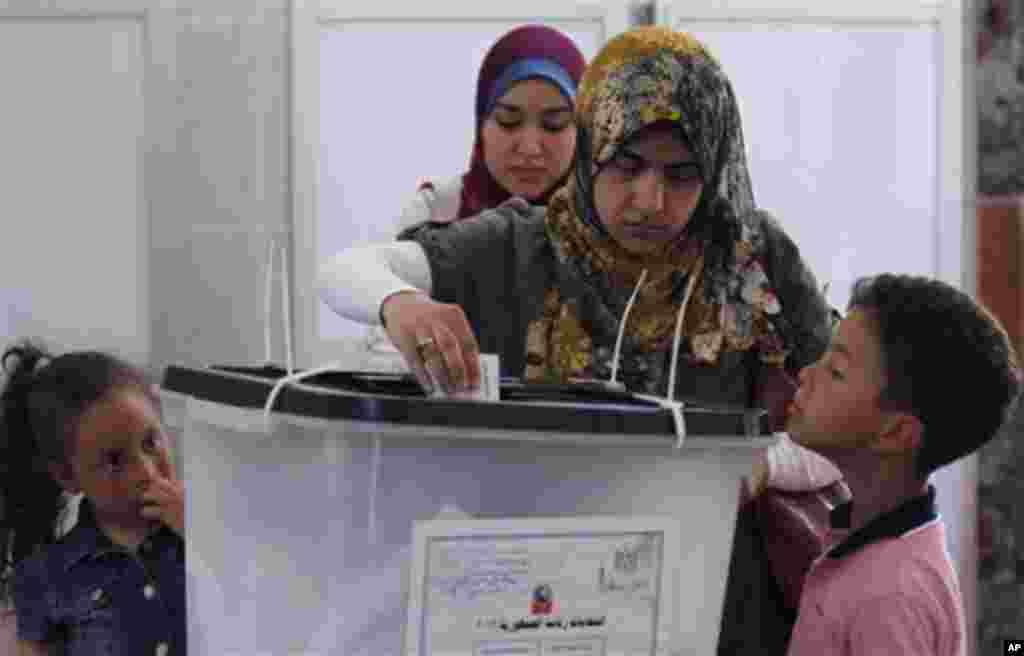 An Egyptian boy looks at his mother as she casts her vote during the second day of the presidential election in a polling station in Alexandria, Egypt, Thursday, May 24, 2012. In a wide-open race that will define the nation's future political course, Egy