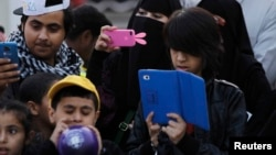 FILE - A family takes pictures with their mobile phones and tablet computer at the 27th Janadriya festival on the outskirts of Riyadh, Saudi Arabia, Feb. 13, 2012.