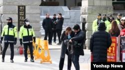 24일 서울 헌법재판소 앞에서 보수단체 회원들이 탄핵반대 집회를 산발적으로 벌이는 가운데 경찰들이 만일의 사태에 대비해 경비를 서고 있다. 한편 경찰은 박근혜 대통령 탄핵심판 사건의 공방이 거세지며 이를 심리하는 헌법재판관의 신변보호를 위해 최근 '24시간 근접경호 요원'을 투입했다.