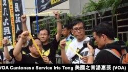 支聯會主席何俊仁在六四遊行終點、北京駐港機構中聯辦門外手持黃絲帶