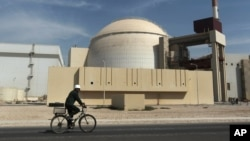 FILE - A bicyclist passes the nuclear power plant just outside Bushehr, Iran, Oct. 26, 2010.